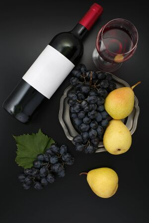Bottle of red wine with label with glass, ripe grapes and pears. Top view 写真素材
