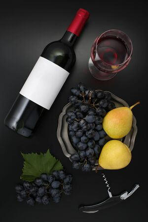 Bottle of red wine with label, corkscrew, pears  and ripe grapes on black. Top view