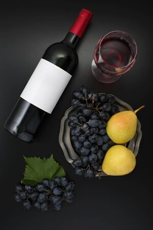 Bottle of red wine with label with glass, ripe grapes and pear. Top view