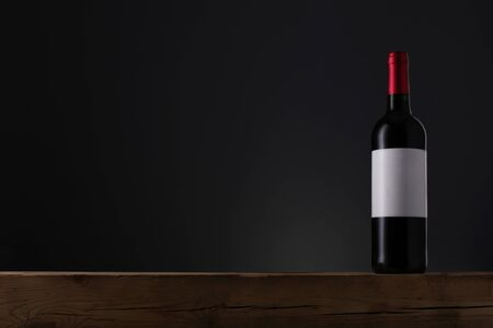 Bottle of red wine with label on old wooden table over grey background
