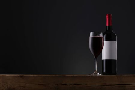 Bottle of red wine with label and wineglass on old wooden table over grey background