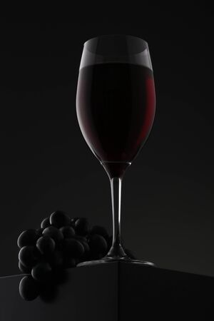 Glass of red wine with grapes over gradient background. Closeup