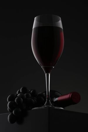 Glass of red wine with grapes and bottle over gradient background. Closeup