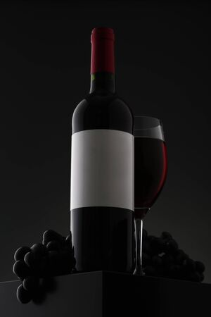 Bottle of red wine with label and wineglass on gradient background. Closeup Stok Fotoğraf