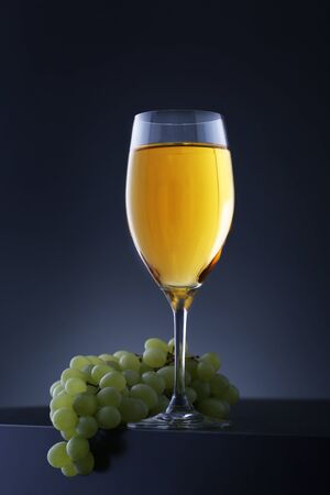 Glass of white wine with grape on black table. Closeup