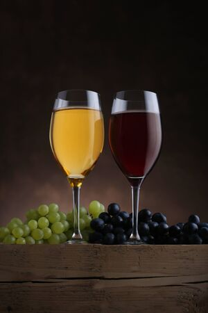 Glasses with red and white wine and grapes on old wooden table. Closeup
