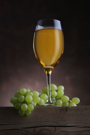 Glass of white wine with grape on old wooden table. Closeup 写真素材