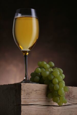 Glass of white wine with grape on oldwooden table. Closeup