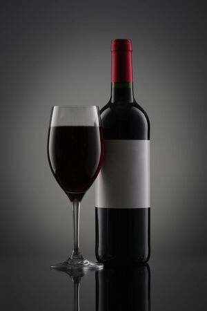 Bottle of red wine with label and wineglass on gray gradient background