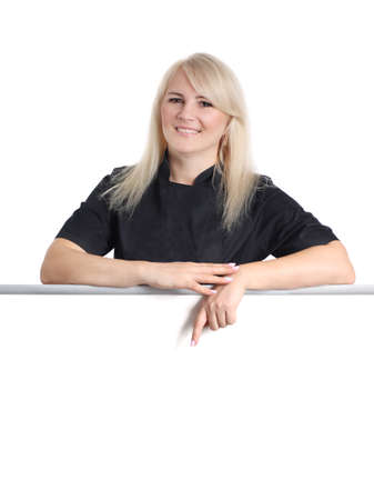 Woman chef in black uniform is showing by finger over empty white board on white background