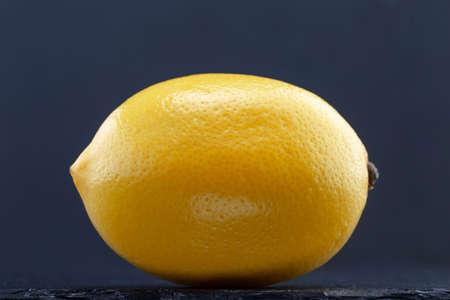 Lemon on black slate stone over gray background. Closeup Stock Photo