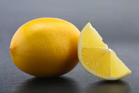 Lemons on black slate stone over gray background. Closeup