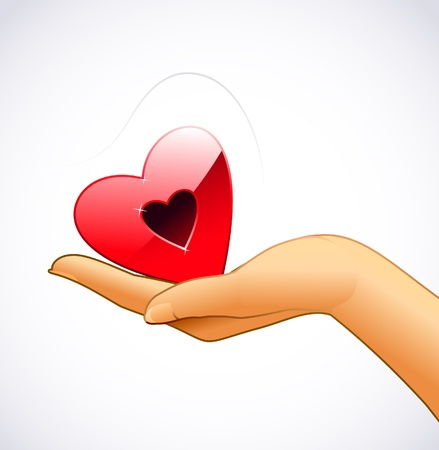 Woman's hand is holding red heart
