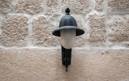 Street lamp black on light stone wall.