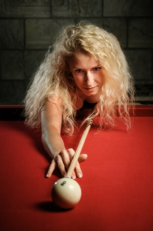 Young woman is playing billiard photo