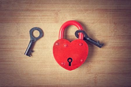 木製のテーブルのキーとハートの南京錠