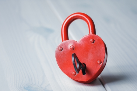 Heart-shaped padlock with key on wooden table