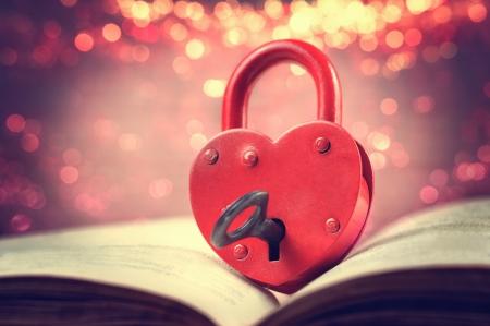 開かれた本のキーにハート型の南京錠