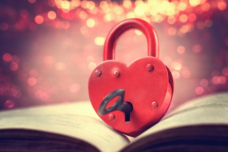 Heart-shaped padlock with key on open book Stok Fotoğraf