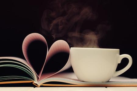 一杯のコーヒーとバレンタイン ハート形の書籍のページ