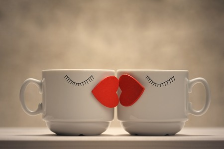 Two coffee cups with red hearts as a kissing lips photo