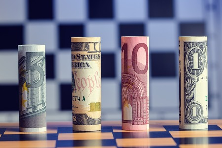 USD and Euro bank notes on chess board photo