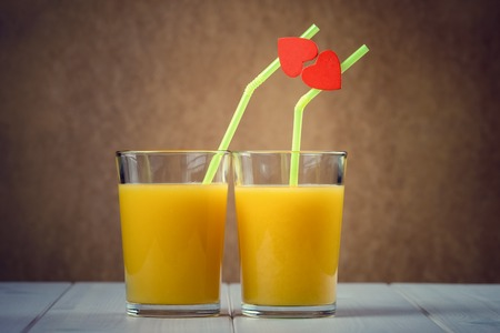 Orange juice glasses with red hearts as a kissing lips photo