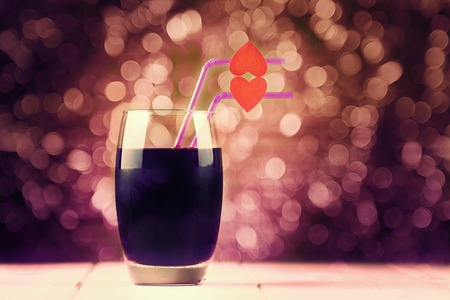 Cherry juice glass with red hearts as a kissing lips on abstract background photo
