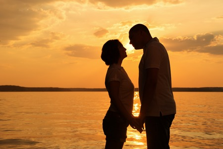 Young romantic couple look to each other during sunset on the beach photo