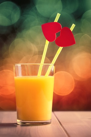 Orange juice glass with red hearts as a kissing lips photo