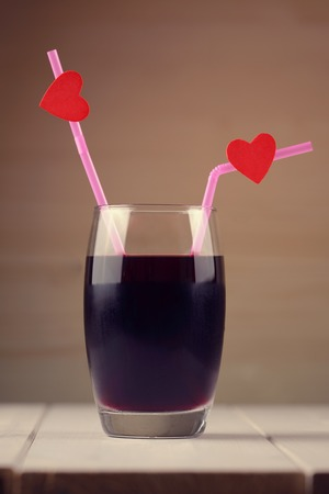 Cherry juice glass with red hearts as a kissing lips photo