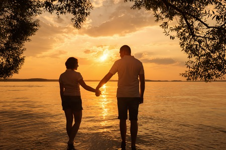 Silhouette of romantic couple walk at sunset photo