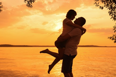 Young couple in love against sunset on the beach photo