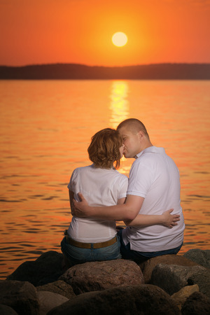 Young couple enjoying a kiss during sunset on the beach photo