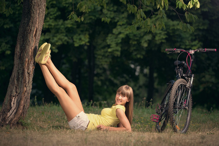 Beautiful young woman is having a rest next to bike in city park photo