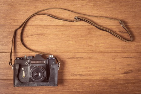 Vintage camera on wooden table. Instagram style toned photo.