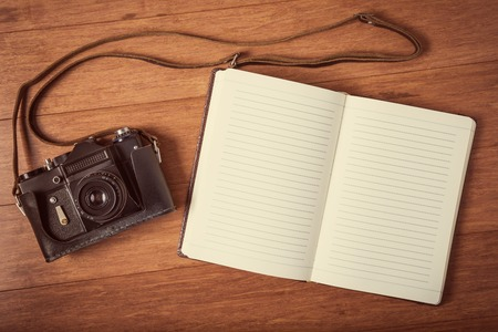 Vintage camera and open diary on wooden table.   style toned photo. photo