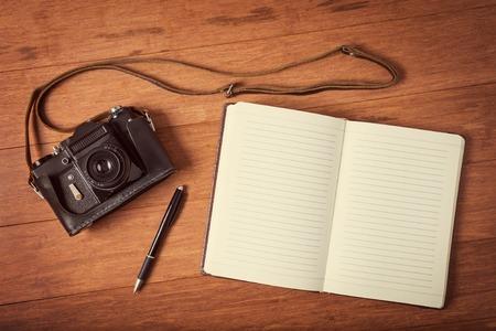 ビンテージ カメラ、木製のテーブルの上のパン日記。Instagram のトーンダウンのスタイルの写真。 写真素材