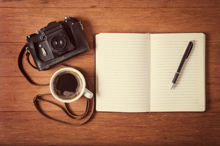 Vintage camera, diary with pan and cup pf coffee on wooden table.  style toned photo. photo