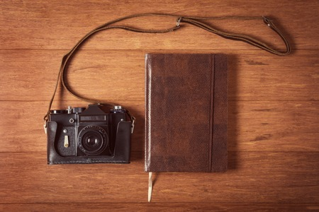 Vintage camera and diary on wooden table, style toned photo. photo