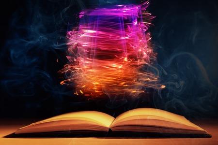 luminescence: Open book with magic lights on dark background Stock Photo