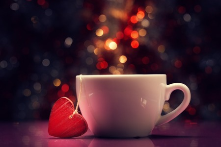 Cup with red heart against defocused lights. photo