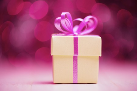 Gift box with pink bow against defocused lights photo
