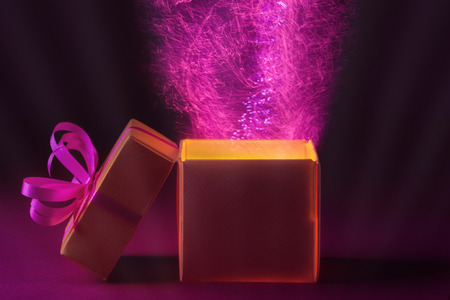 Open holiday box with magic light on dark background photo