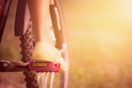 Low viewing angle of woman leg on mountain bike pedal photo