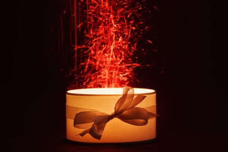 Open gift box with magic light on dark background photo