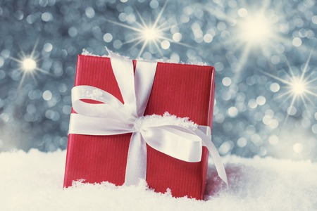 Red gift box in snow against abstract background with star luminous effect photo