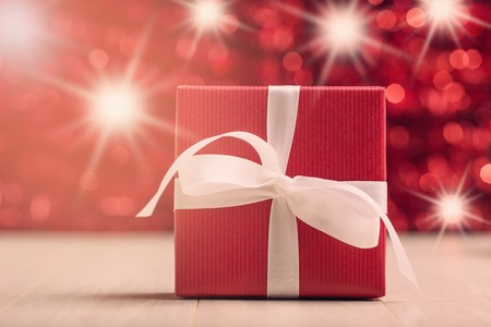Red gift box against abstract background with star luminous effect photo