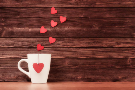day dream: White cup with heart shapes over vintage wooden background