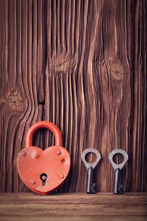 ヴィンテージの木製の背景にハート型のロックと 2 つのキー
